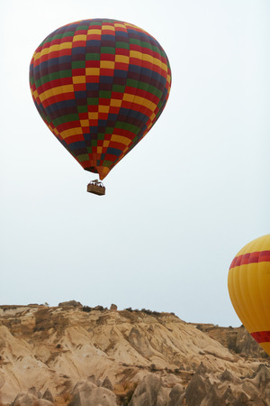Colorful Hot Air Balloon With Basket Flying In Sky Above Land, Traveling In Balloon. High Resolution Standard-Bild - 115069406