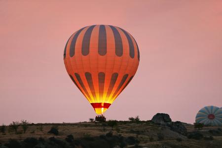 Hot Air Balloon With Fire Light At Morning Valley In Cappadocia Turkey. High Resolution Standard-Bild - 115069411
