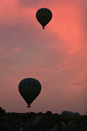 Hot Air Balloons Silhouettes Flying In Red Sky Above Valley At Cappadocia. High Resolution Standard-Bild - 115069414
