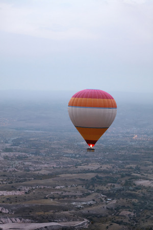 Colorful Hot Air Balloon Flying In Foggy Sky Above Fields With Burner Firing Up, Ballooning At Cappadocia. High Resolution Stock Photo