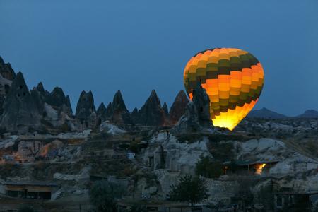 Colorful Hot Air Balloon Illuminating Behind Rock Formations In Night, Ballooning At Cappadocia Turkey. High Resolution Standard-Bild - 115069417