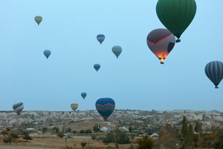 Travel. Colorful Hot Air Balloons Flying Above Cappadocia Early In Morning, Ballooning In Nature. High Resolution