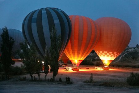 Hot Air Balloons With Fire Lights Before Flying In Early Morning In Cappadocia Turkey. High Resolution Standard-Bild - 115069425
