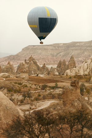 Travel. Hot Air Balloon Flying Above Rock Valley, Ballooning In Cappadocia Turkey. High Resolution Standard-Bild - 115069434