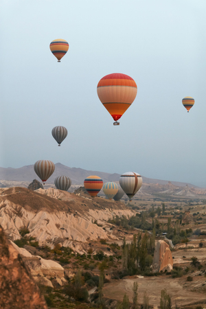 Hot Air Balloons In Sky. Colorful Flying Balloons In Nature Above Stone Hills. High Resolution Standard-Bild - 115069436