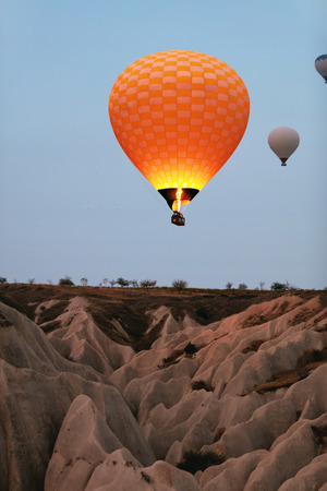 Orange Hot Air Balloon With Burner Firing Up Flying In Sky Above Rock Formations In Nature. High Resolution Standard-Bild - 115069437