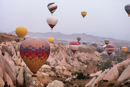 Hot Air Balloons In Sky. Colorful Flying Balloons In Nature Above Stone Hills. High Resolution Standard-Bild - 115069438
