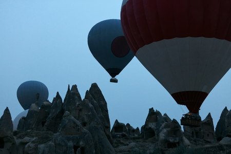 Hot Air Balloons Silhouettes Flying Above Rocks Early In Morning, Ballooning In Mountains. High Resolution Standard-Bild - 115069443