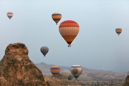 Hot Air Balloons In Sky. Colorful Flying Balloons In Nature Above Stone Hills. High Resolution Standard-Bild - 115069444