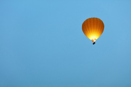 Travel. Yellow Hot Air Balloon With Fire Light Flying In Clean Blue Sky, Ballooning. High Resolution