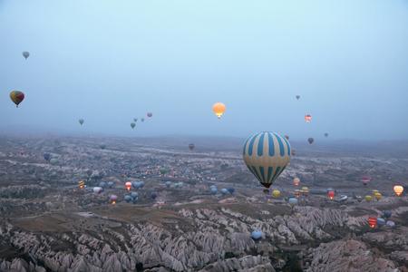 Colorful Hot Air Balloons Flying In Sky Above Rock Valley At Cappadocia Turkey. High Resolution Standard-Bild - 115069450