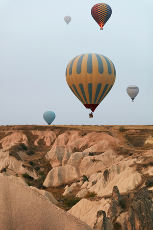 Hot Air Balloons In Sky. Colorful Flying Balloons In Nature Above Stone Hills. High Resolution Standard-Bild - 115069676