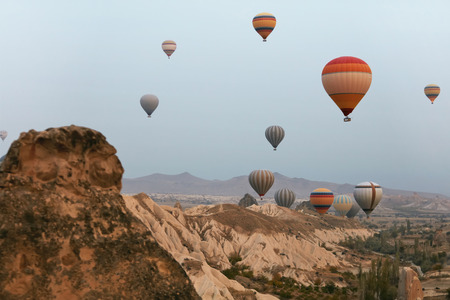 Hot Air Balloons In Sky. Colorful Flying Balloons In Nature Above Stone Hills. High Resolution Standard-Bild - 115069679