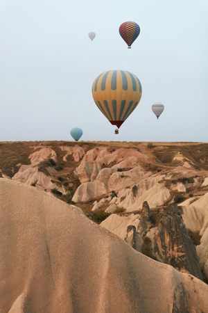 Hot Air Balloons In Sky. Colorful Flying Balloons In Nature Above Stone Hills. High Resolution Stock Photo