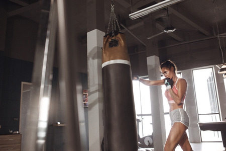 Sports. Woman boxer doing boxing training or workout at gym. Female in sportswear hitting huge punching bag at boxing studio