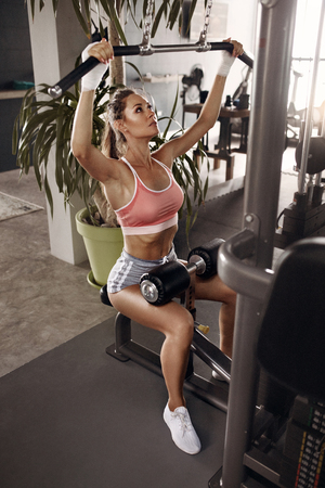 Gym workout. Woman exercising, doing front lat pulldown exercise. Female athlete in sexy sportswear training body at sport club