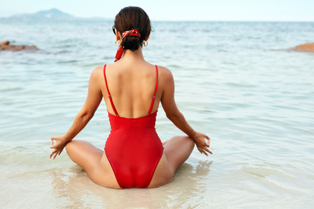 Yoga Meditation. Woman Relaxing At Sea Beach Back View. Girl In Red Swimsuit In Lotus Pose. High Resolution