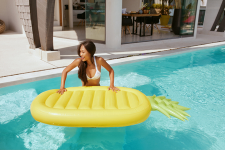 Summer vacation. Woman in bikini swimsuit with pineapple float in swimming pool. Asian girl relaxing with pool toy at luxury resort outdoors