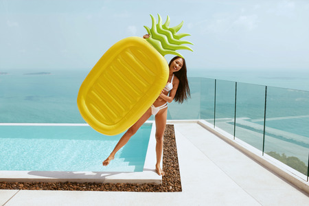 Summer fun. Happy girl near infinity swimming pool with pineapple float enjoying vacation. Smiling woman with pool toy outdoors on sunny day