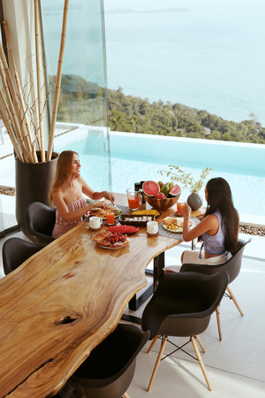 Women eating breakfast at dinning room at luxury hotel outdoors. Female friends sitting at table, enjoying morning meal at resort with sea and pool on background.