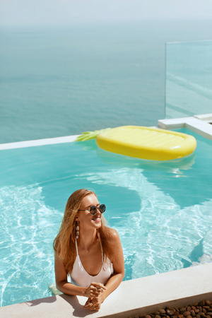 Summer vacation. Woman in fashionable sunglasses relaxing in swimming pool. Girl model in infinity pool with pineapple float on water and sea on background