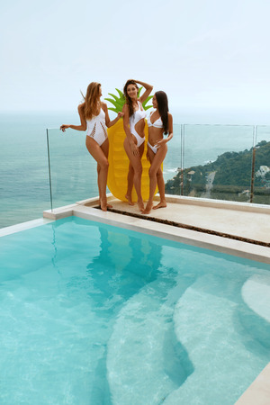 Women summer fashion. Girls in stylish white swimsuits near infinity swimming pool with pineapple float and sea on background at luxury resort hotel
