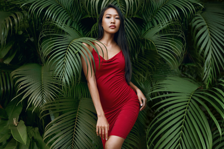Fashion. Woman model in red dress with green palm leaves on background. Beautiful asian girl in fashionable summer clothes and earrings posing in tropical nature portrait 免版税图像