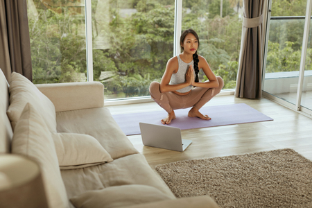 Yoga at home. Woman training body near computer in morning. Beautiful asian girl practices garland pose near laptop in living room Stockfoto