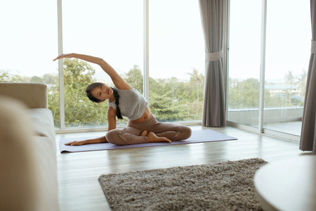 Yoga fitness. Girl training, stretching body at home in morning. Beautiful asian woman with fit body in sport clothes practices yoga pose on mat in living room
