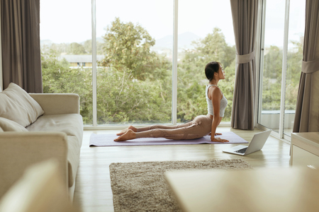 Girl doing yoga training, stretching body at home with computer. Beautiful asian woman practices cobra pose on yoga mat with laptop near window in living room in morning