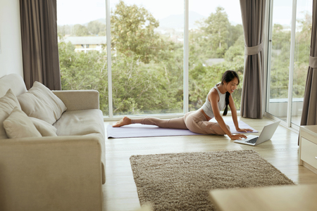 Girl doing yoga training at home while using computer. Beautiful asian woman practicing pigeon pose, stretching body on yoga mat and watching tutorial on laptop in living room