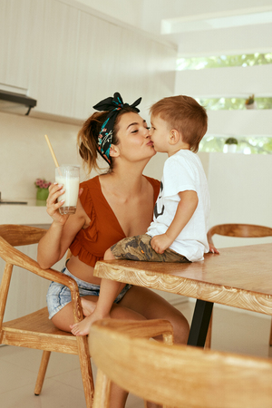 Mother kissing her child at table in kitchen in morning. Woman kisses boy while having a glass of healthy vegan milk for breakfast