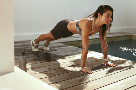 Body workout. Woman in sportswear doing plank exercise outdoors. Athletic girl with fit body in sportswear planking on street