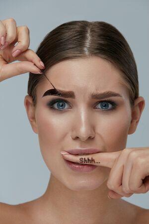 Cosméticos para cejas. Mujer quitándose el tinte de gel para cejas de la ceja sosteniendo el dedo en el monte con letras shhh en primer plano. Modelo de niña pelando producto de belleza
