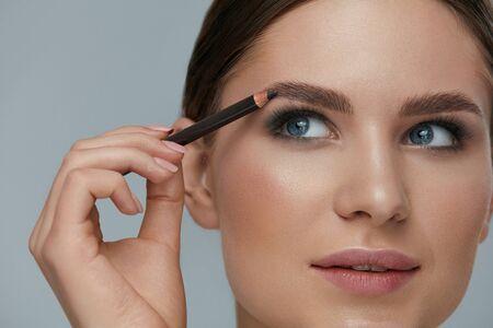 Makijaż kosmetyczny. Kobieta kształtowania brwi z ołówkiem do brwi zbliżenie. Modelka z profesjonalnym makijażem do konturowania brwi Zdjęcie Seryjne