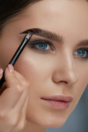 Eyebrow coloring. Woman applying brow tint with makeup brush closeup. Girl model using liquid peel-off brow gel, beauty product on eyebrows 스톡 콘텐츠