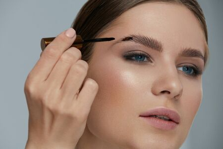 Eyebrow coloring. Woman applying brow tint with makeup brush closeup. Girl model using liquid peel-off brow gel, beauty product on eyebrows Stock Photo