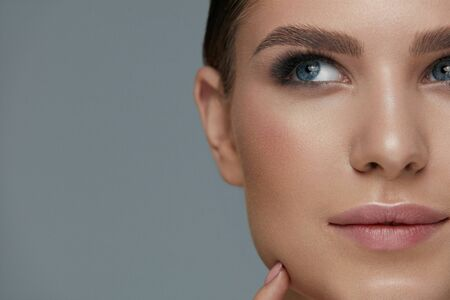 Beauty makeup. Woman face with beautiful eyes and eyebrows make-up and long black eyelashes closeup