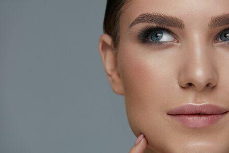 Schoonheid make-up. Vrouw gezicht met mooie ogen en wenkbrauwen make-up en lange zwarte wimpers close-up Stockfoto