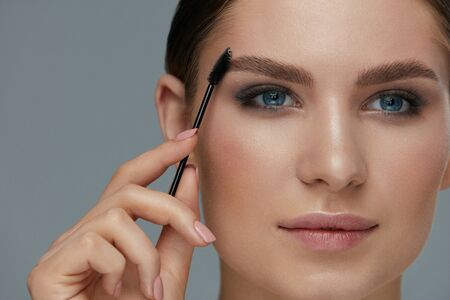 Eyebrow makeup. Woman brushing brows with brush closeup. Girl model with beautiful eyes shaping eyebrows with brow gel