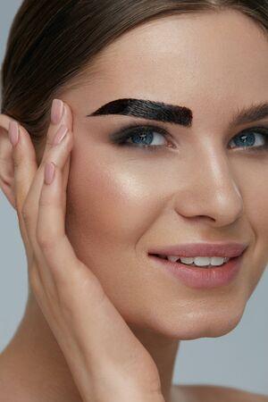 Maquillaje de belleza. Ceja para colorear de mujer con primer plano de tinte de gel. Modelo de niña que fija el gel líquido peel-off para cejas en la ceja