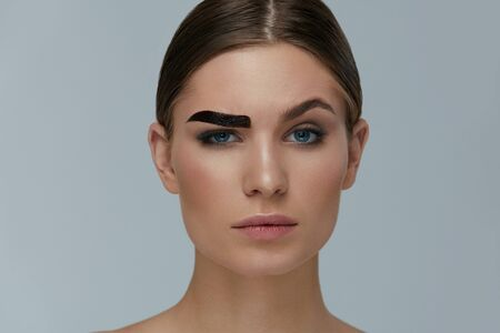 Beauty makeup. Woman coloring eyebrow with gel tint portrait. Girl model setting liquid peel-off brow gel on eyebrow