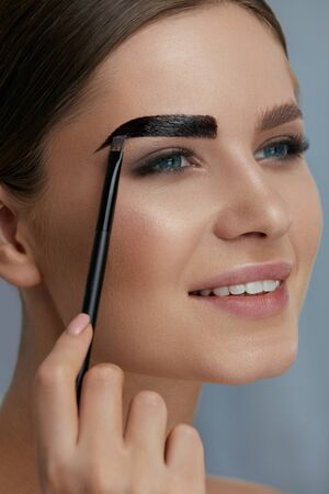 Eyebrow coloring. Woman applying brow tint with makeup brush closeup. Girl model using liquid peel-off brow gel, beauty product on eyebrows 写真素材