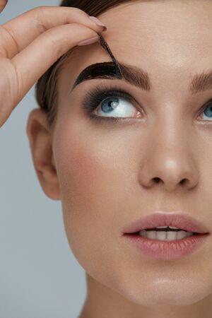 Kosmetyki do brwi. Kobieta zdejmując odcień żel do brwi z zbliżenia brwi. Model dziewczyny złuszczający produkt kosmetyczny do brwi