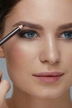 Beauty makeup. Woman shaping eyebrow with brow pencil closeup. Girl model with professional makeup contouring eyebrows