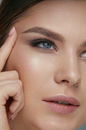 Schönheitsgesichts-Make-up. Frau mit schönen Augen und Augenbrauen-Make-upnahaufnahme. Mädchenmodell, das Augenhaut mit dem Finger anhebt