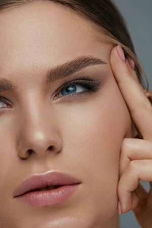 Beauty face makeup. Woman with beautiful eyes and eyebrows make-up closeup. Girl model lifting eye skin with finger