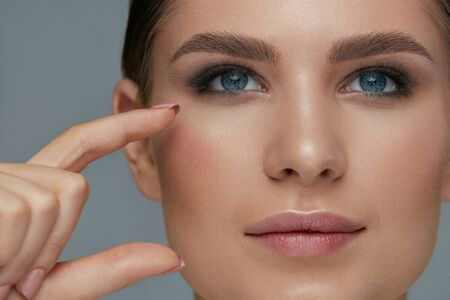Beauty face makeup. Woman with beautiful eyes and eyebrows make-up closeup. Girl model with fingers near facial skin
