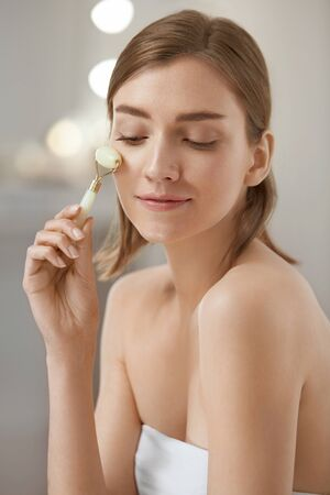 Woman using jade facial roller for face massage at home. Girl using natural massager tool for skin care and spa beauty treatment closeup portrait