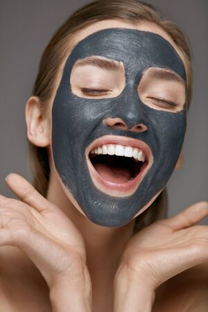 Beauty face skin care. Woman with cosmetic spa facial mask. Smiling girl model with grey clay mask and beautiful white smile closeup portrait Stock Photo - 124606944